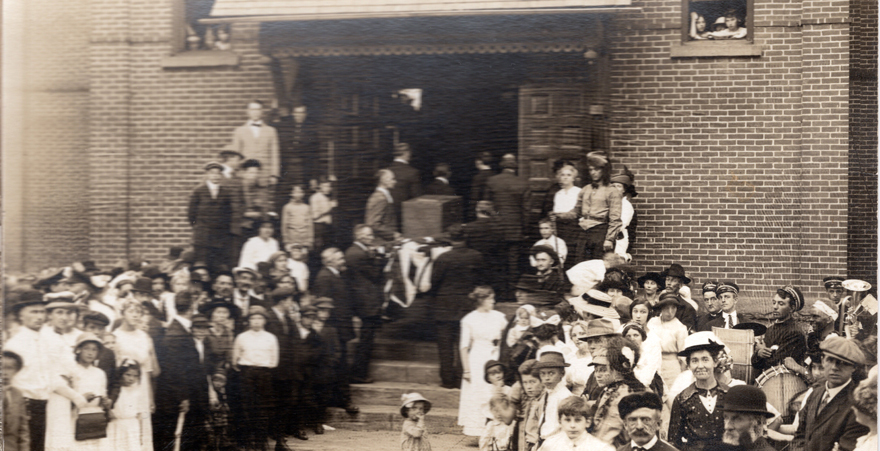 A crowd gathers around Sauk City High School as participants in Ethel Rockwell's  A Social Center Pageant move the town ballot box from City Hall to the high school  in a gesture that represents the convergence of citizenship and education. Courtesy of the Sauk Prairie Area Historical Society