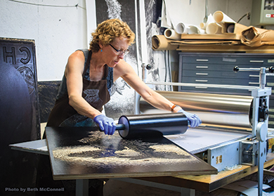 SV Medaris rolls ink on a large woodcut in her studio. Photo by Beth McConnell.