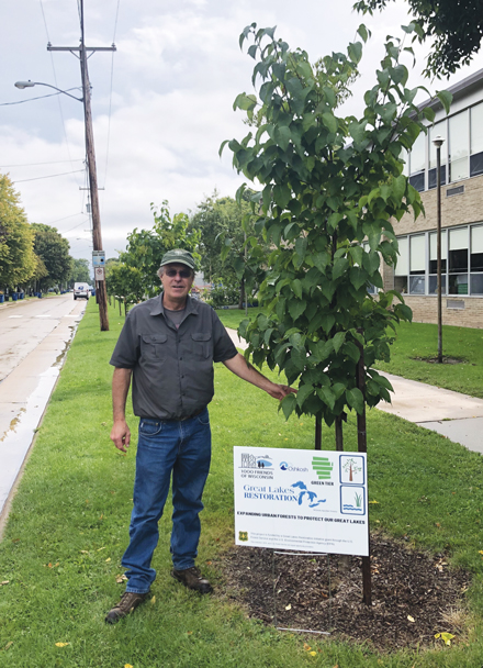 Bill Sturm, Oshkosh City Forester & Landscape Operations Manager, stands in front of a young redbud tree planted by the city to help capture rainfall. Sturm's work is part of a larger, statewide initiative through 1000 Friends of Wisconsin that draws on a U.S. Forest Service grant through the Great Lakes Restoration Initiative to reduce runoff and improve water quality. Photo credit: Abe Lenoch/1000 Friends of Wisconsin.
