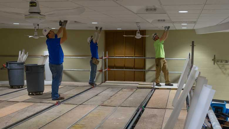 Energy conservation measures under way at UW–Stevens Point include upgrading lights to energy efficient LED lights. Here (l to r), Andy Klessig, Jose Rodriguez and Patrick Houlihan of Faith Technologies replace lighting in a Science Building lecture hall.