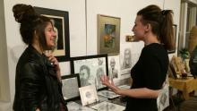 Appleton-based CSA artist Ali Fuller (right) chats with a shareholder near a display  of her drawings.