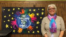 Author Lisa Vihos at I.D.E.A.S. Academy with the poster made by high school students in Stuart Howland's graphic design class.
