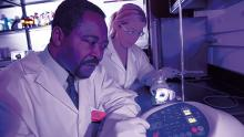 """Chukuka S. Enwemeka, dean of UWM's College of Health Sciences, conducts an experiment with research associate Violet Bumah. Among Enwemeka's discoveries in phototherapy research: blue light in a certain wavelength kills the antibiotic-resistant """"superbug"""" form of Staphylococcus aureus."""