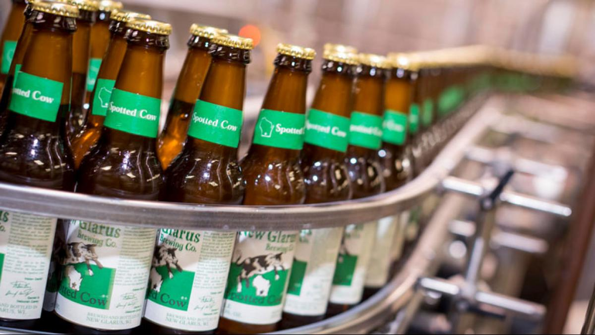 Bottles of New Glarus Brewing Company's signature beer come off the production line. Soon, all New Glarus bottles will be sourced from Ardagh glass manufacturing plant in Burlington, adding another dimension to the Spotted Cow tagline: Only in Wisconsin. Photo by Andy Manis.