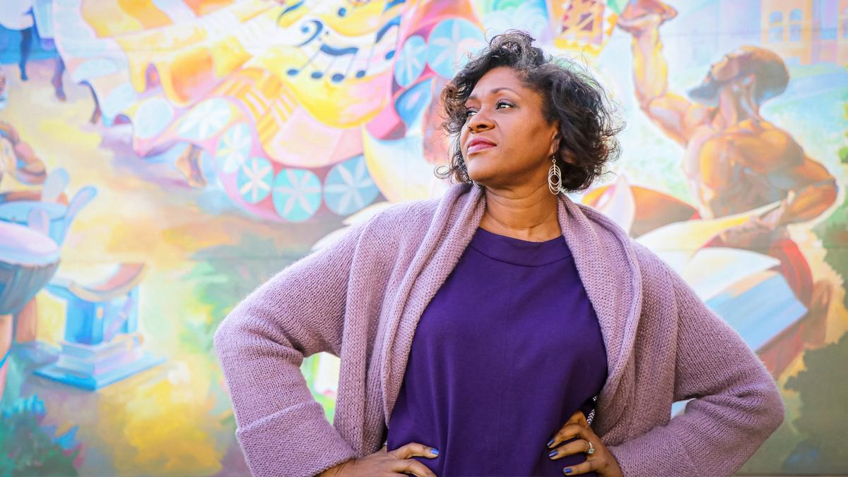 Wisconsin Poet Laureate Dasha Kelly Hamilton stands in front of The Rebirthing of the Earth Mother, a mural artist Tia Richardson created in 2018 for an exterior wall of the Historic Garfield Apartments (originally Garfield Street School) in Milwaukee's Bronzeville neighborhood. Photo by TJ Lambert/Stages Photography