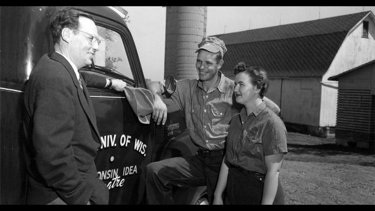 """Robert Gard visits with farmers on May 9, 1955. Gard traveled across the state (note the Wisconsin Idea Theater logo painted on the side of his truck) to promote and cultivate the theatrical arts in rural communities. Gard was a well-known figure in Wisconsin through his travels as well as his WHA-Radio program, and later WHA-TV program, """"Wisconsin Is My Doorstep.""""  UW Digital Collections/ID S15183"""