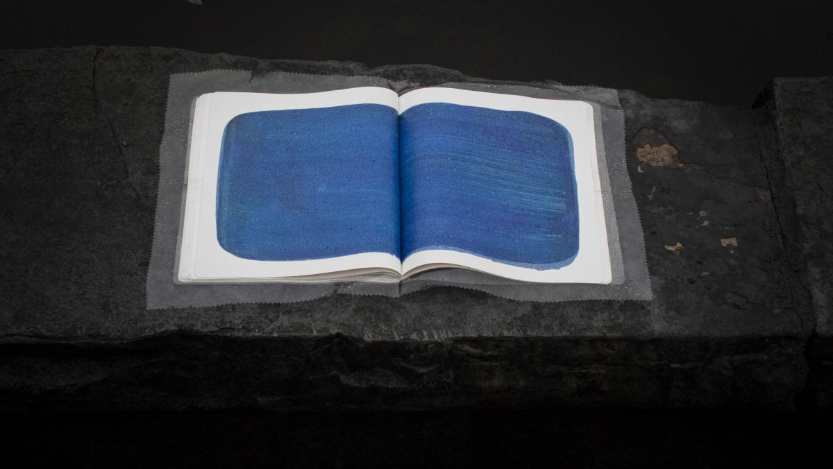 """Helen Hawley, Come If You Won't Stay Long [installation shot], 2017, artist's book 11 1/2"""" x 9 1/2"""" x 1/2"""", ed. 40; litho on rubber cover, inkjet on polymer paper, aluminum slipcase, rain jacket made from TPU fabric"""