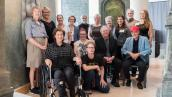 Artist Terese Agnew (in wheelchair after an art-related accident) and her collaborators for the epic Writing in Stone installation. Photo by Studio Indigo Photography.