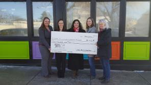 Karen Carlock (second from right) poses in front of the BECM with a donation from the State Bank of Cross Plains.