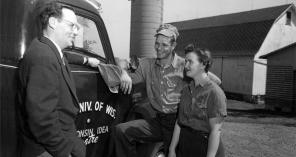 "Robert Gard visits with farmers on May 9, 1955. Gard traveled across the state (note the Wisconsin Idea Theater logo painted on the side of his truck) to promote and cultivate the theatrical arts in rural communities. Gard was a well-known figure in Wisconsin through his travels as well as his WHA-Radio program, and later WHA-TV program, ""Wisconsin Is My Doorstep.""  UW Digital Collections/ID S15183"