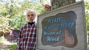 Blei on his own turf in Ellison Bay, Door County, standing in front of a sign welcoming—or, considering the coyote, possibly warning away—visitors to his converted chicken coop writer's studio. Photo Credit: John Nelson