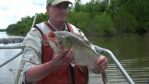 Moy holds a bighead carp caught on a recent trip to Havana, Illinois, on the Illinois River near Lake Chautauqua