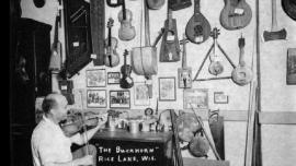 Otto Rindlisbacher, folk singer and maker of stringed instruments, sitting in his shop holding a Hardanger fiddle. Photo ca. 1941 by folklorist Helene Stratman-Thomas. Reprinted by permission of the Wisconsin Historical Society (WHS: #25413).