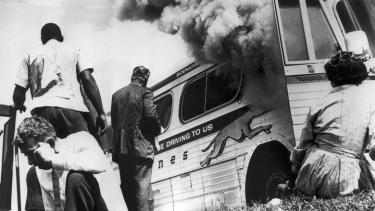 """A """"Freedom Bus"""" in flames, six miles southwest of Anniston, Alabama, May 14, 1961. (Birmingham Public Library/Oxford University Press)"""