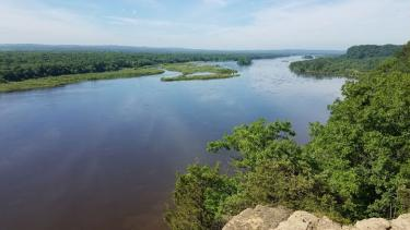 The view down the Wisconsin River from Cactus Bluff in Ferry Bluff State Natural Area. Millions of years ago this valley was carved to a depth of over 600 feet by an ancient river. The last major glaciation deposited as much as 300 feet of sand and gravel, resulting in the broad floodplain and terraces that characterize the Lower Wisconsin River valley today. Photo by Eric Carson.